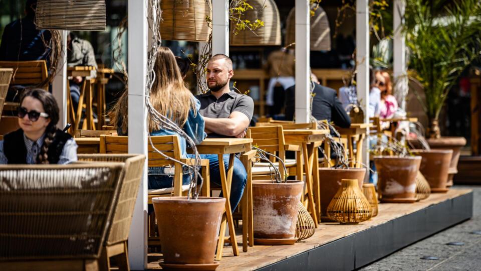 Na ilustračnej snímke zákazníci sedia na terase prevádzky na nábreží Dunaja.