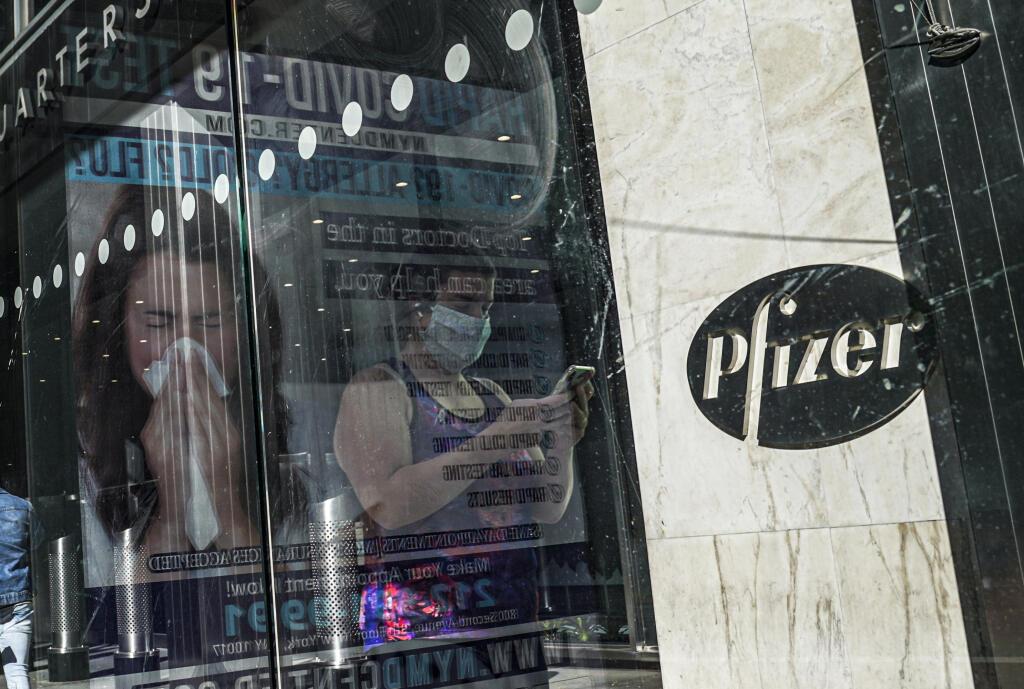 KK27 New York - Na archívnej snímke z 9. novembra 2020 svetové sídlo Pfizeru v NewYorku. Spoločnosti Pfizer a BioNTech požiadajú americký úrad na kontrolu potravín a liekov FDA (Food and Drug Administration) o povolenie na núdzové použitie pre svoju vakcínu proti novému koronavírusu. FOTO TASR/AP FILE - In this Nov. 9, 2020, file photo, an ad for COVID-19 testing reflects on glass at a bus stop, as pedestrians walk past Pfizer world headquarters in New York. On Friday, Nov. 20, 2020, Pfizer has